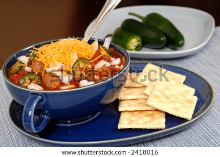 A bowl of spicey chili and crackers with jalapeno peppers