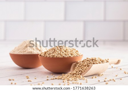 A Bowl of Sprouted Sorghum and Sorghum Flour on a Bright White Table Zdjęcia stock ©