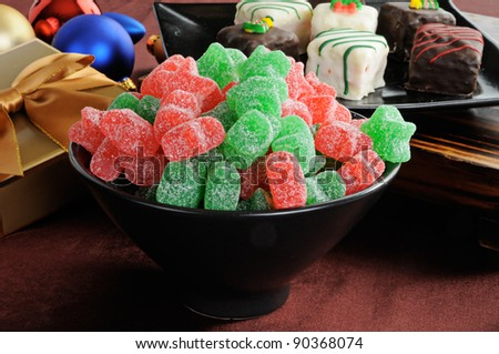 A bowl of star shaped red and green gum drops, petit fours and Christmas decorations