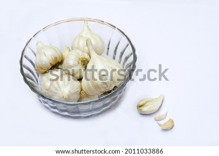 A bowl of strong-smelling bulbs of garlic used as a flavoring in cookery, isolated on white Stock photo ©