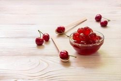 A bowl of sugared cherry fruits or spoon sweet cherries on a light wooden background, copy space. Horizontal.
