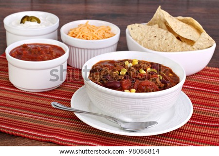 A bowl of taco soup surrounded with condiments including sour cream, salsa, tortilla chips and shredded cheddar cheese.
