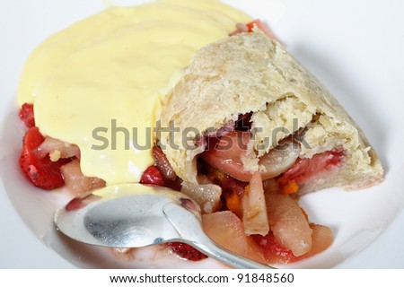 A bowl of traditional British steamed fruit pudding, of pears and strawberries with a sweet suet pastry crust, custard and an old-fashioned spoon