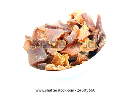 A bowl of traditional South African Biltong, a cultural snack of raw dried meat cut into slices. Image isolated on white background.
