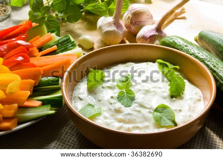 A bowl of tzatziki dip and fresh cut vegetable sticks next to it - stock photo