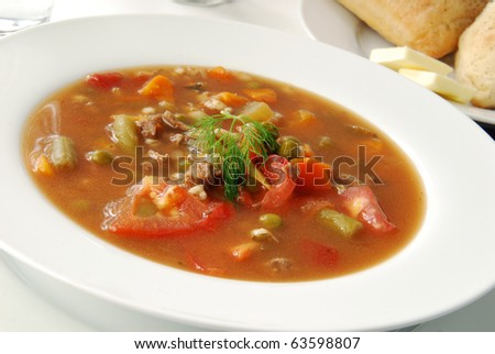 A bowl of vegetable beef soup garnished with a sprig of dill