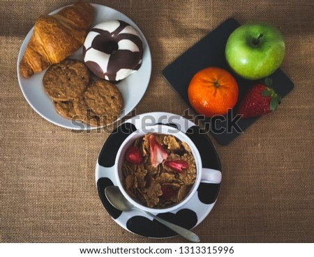A bowl with cornflakes and red berries and a plate of black slate with a green apple, a tangerine and a strawberry and one plate with one croissant, one chocolate donut and cookies on a burlap #1313315996