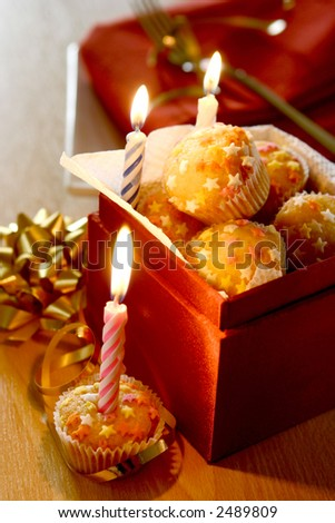 A box full of mini star fairycakes as individual birthday cakes to be shared, three symbolic candles lit up. - stock photo