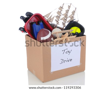 A box full of toys and sports equipment for a holiday charity drive. Isolated on white with reflection.