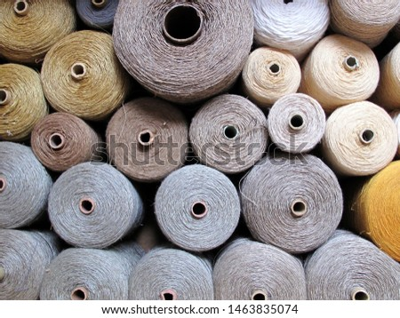 A box full of yarn cones in different sizes. arranged, in order and member. Discreet colours in white, silver, iron, light blue, beige and some yellow. Stockfoto ©