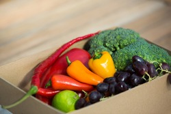 A box of market fruit and vegetables. Healthy nutritious rainbow coloured food in a box. Close up. Home grown organic vegan food.