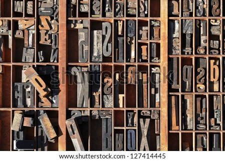 A box of old vintage printing press letter blocks in a old wooden box