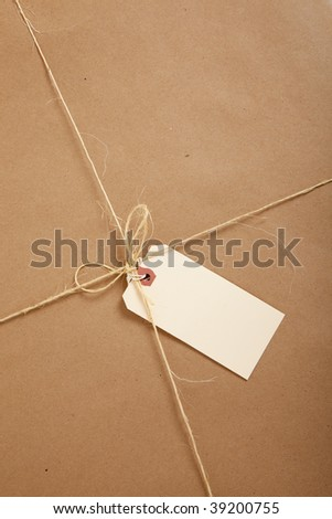a Box wrapped in brown craft paper with a blank tag on a white background