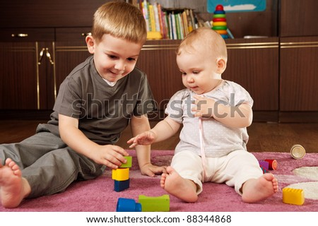 A boy aged 3 and a girl aged 1 are playing on the floor