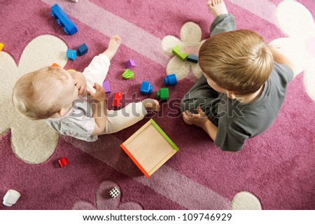 A boy aged three and a girl aged one are playing on the floor.View from above.