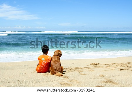 A boy and a dog sitting on the beach