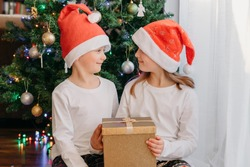 A boy and a girl in Christmas hats are sitting under a Christmas tree with a gift box in their hands and looking at each other. Happy childhood. New year holiday, gift giving