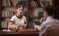 A boy and a girl play chess, teenagers play a board game, sports interest, schoolchildren are sitting at the table, learning to play chess.