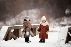 A boy and a girl stand on a snow-covered wooden bridge. The boy holds a lantern in his hands. Children in warm sheepskin coats and hats. Image with selective focus.