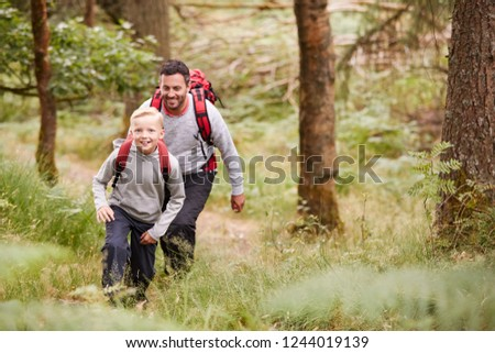 A boy and his father walking together on a trail between trees in a forest, both smiling, elevated view