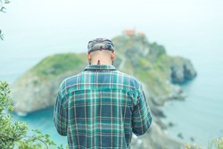 A boy at the top of San Juan de Gaztelugatxe. In a hipster plaid shirt and cap, his back is looking at the landscape. As a background the sea with dragonstone in the middle of the sea.