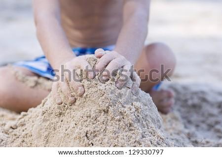 A boy building the sandcastle on the beach focus on hands