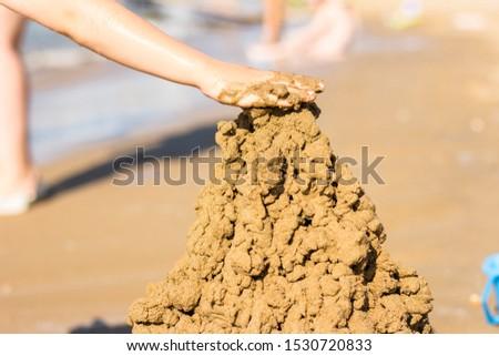 A boy builds a sand castle on the beach Сток-фото ©