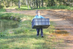 a boy carries a plastic basket next to the pond. child with a large basket, containers, in the hands of nature.