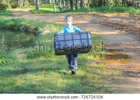 a boy carries a plastic basket next to the pond. child with a large basket, containers, in the hands of nature. #726726106