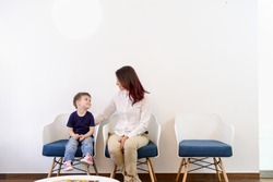 A boy child in doctors waiting room - reception with his mom. Kids first visit for a regular dentist exam