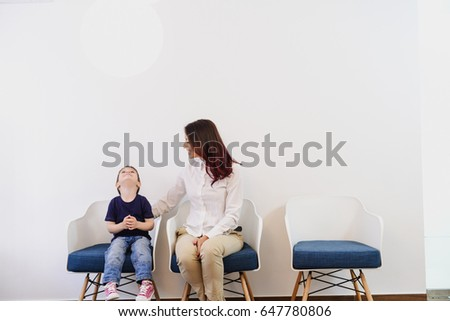 A boy, child in doctors waiting room - reception with his mom. Kids first visit for a regular dentist exam #647780806