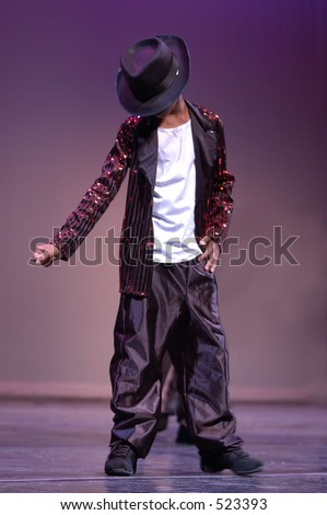 A boy dances on the stage imitating Micheal Jackson.