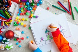 A boy draws a Christmas tree. Child's drawing Christmas. The child lies on the floor and draws in a notebook with white paper.