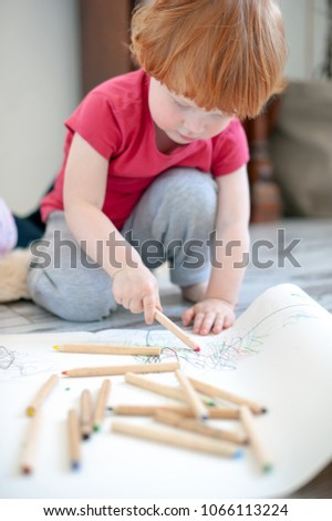 A boy draws with pencils sitting on the floor #1066113224