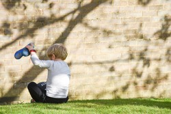 A boy empties a stone from his shoe while playing outside