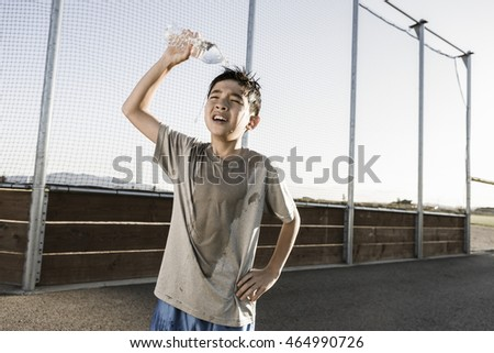 A boy exhausted after a hard practice pours cool water over his head.