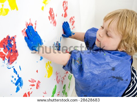 A boy finger painting with blue acrylic paint on a wall