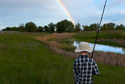 a boy fishing in the summer near a lake in a field, he walked along a path with a fishing rod, saw a rainbow in the sky and the sunset, catches a fish sitting on a chair