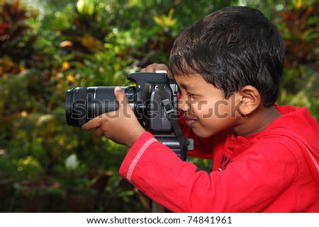 A boy focusing with a camera fixed on tripod