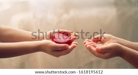 A boy gives a red heart to a girl. Love as a gift. Hands close up.