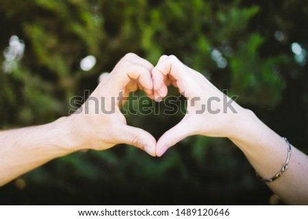 A boy hand and woman hand making a heart #1489120646
