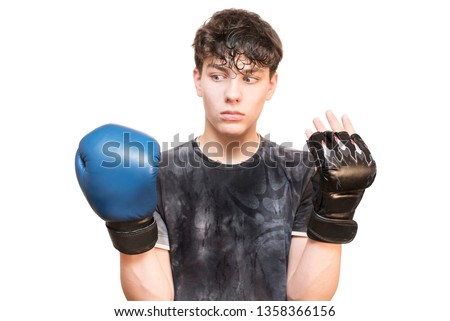 A boy has on one hand boxing mitten on other hand mitts of mixed martial arts. A teen likes to engage in mixed martial arts, but recently he likes boxing. He chooses what kind of sports to take #1358366156