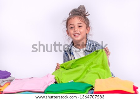 a boy holding green tee shirt behind colorful pile of tee shirts in tee shirt shop on white background