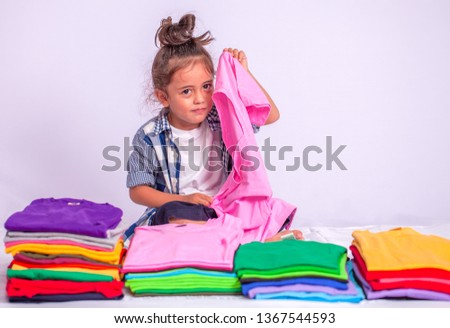 a boy holding pink tee shirt behind colorful pile of tee shirts in tee shirt shop on white background