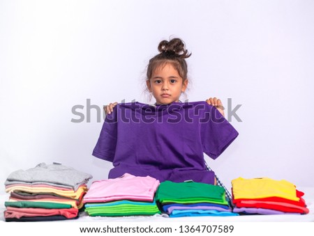 a boy holding purple tee shirt behind colorful pile of tee shirts in tee shirt shop on white background