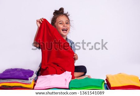 a boy holding red tee shirt behind colorful pile of tee shirts in tee shirt shop on white background