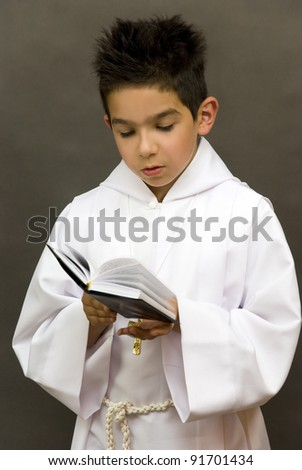 A boy holds a rosary and prayed first communion