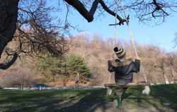 a boy in a hat, a jacket with fur and rubber boots swinging on a makeshift swing
