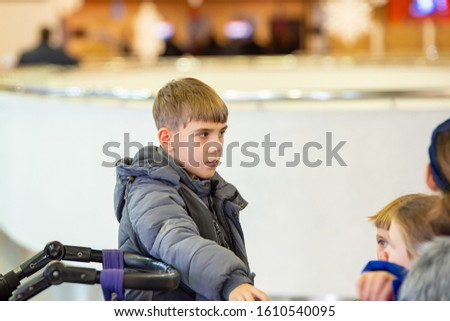 A boy in a jacket eats a roll and looks around.