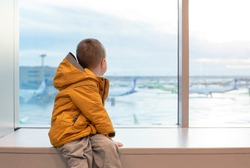A boy in a yellow jacket at the airport at the big window.